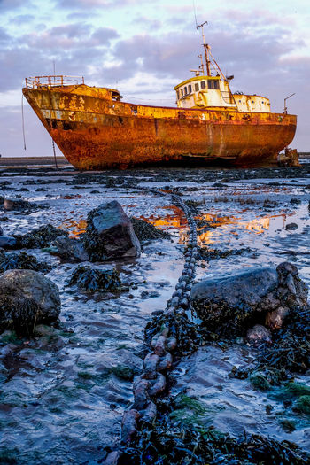 Abandoned Bad Condition Beach Beauty In Nature Boat Cloud - Sky Damaged Day Deterioration Mode Of Transport Moored Nature Nautical Vessel No People Obsolete Outdoors Rock - Object Run-down Rusty Sea Ship Sky Transportation Travel Water
