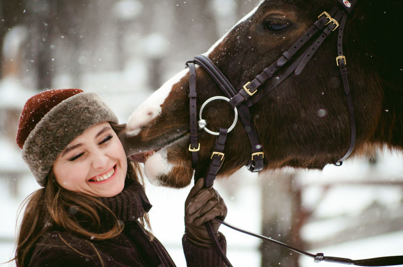 Cheerful Close-up Cold Temperature Day Domestic Animals Happiness Headshot Horse Human Body Part Human Hand Lifestyles Livestock Mammal One Animal One Person Outdoors People Real People Smiling Snow Standing Warm Clothing Winter Young Adult Young Women