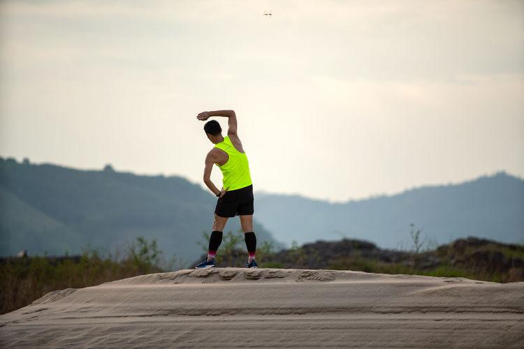 Rear view of man skateboarding on mountain against sky