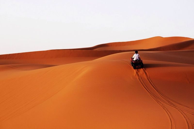 Rear View Of Man Riding Quad Bike On Sand Dune Against Clear Sky