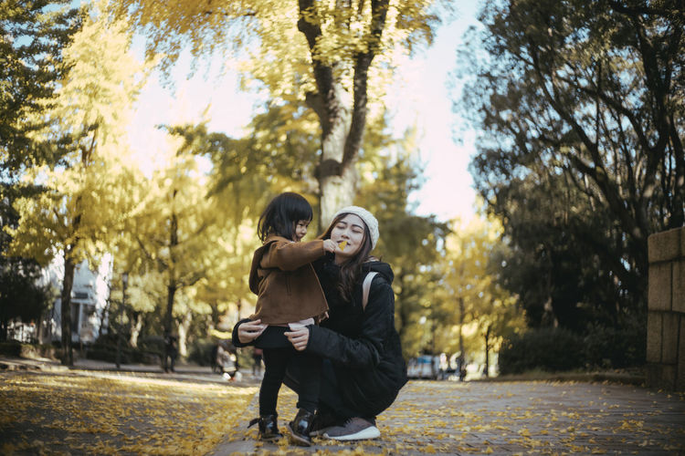 Mother with daughter in park during autumn