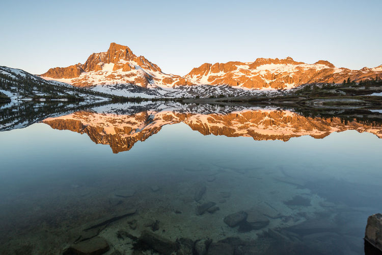 Soaked in tranquility of nature | One of the iconic images that I'd seen over and over again and that I had planned to take as my own was the orange glow cast on Mt. Ritter and Banner Peak at sunrise. And, of course, the reflection of it in Thousand Island Lake. While there was not a single speck of cloud in sight, no wind was disturbing the tranquility of the water. It was so calm that those small ripples created by the trouts travelled far. A school of rainbow trouts indifferently swimming me by put a big smile on my face. As the sun rose, the peaks started glowing from grey to dark red to orange. Transfixed on the magic happening before my eyes, I simply let myself soaked in the tranquility of nature. Thousand Island Lake, CA Banner Peak Mt. Ritter Thousand Island Lake Beauty In Nature Clear Sky Eastern Sierra Glow Idyllic Lake Mountain Range Mountains Nature No People Non-urban Scene Reflection Lake Reflections Scenics - Nature Sierra Nevada Sky Sunrise Symmetry Tranquil Scene Tranquility Water Wilderness