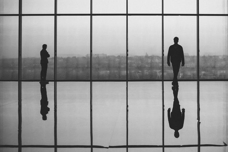 Silhouette Men Against Glass Window