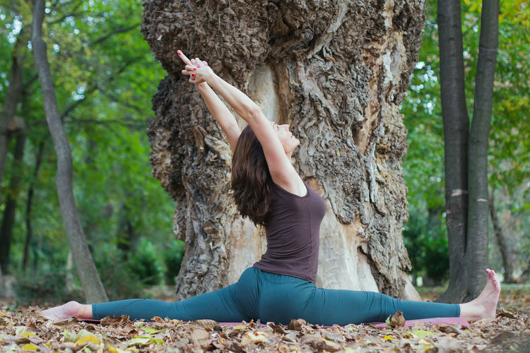 Woman climbing on tree trunk in forest