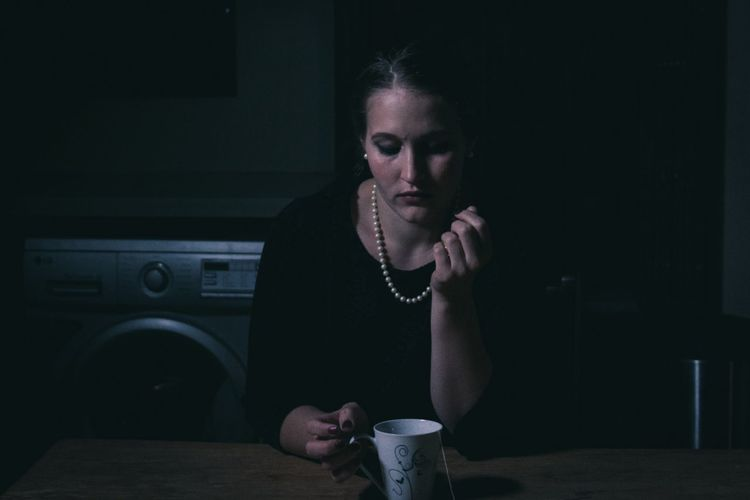 Thoughtful young woman with cup sitting at table