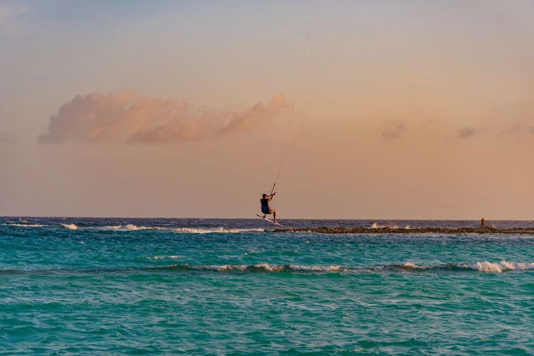 Man kiteboarding over sea against sky during sunset