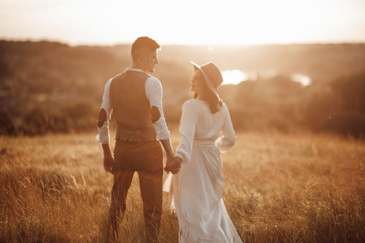 Rear view of couple standing on land