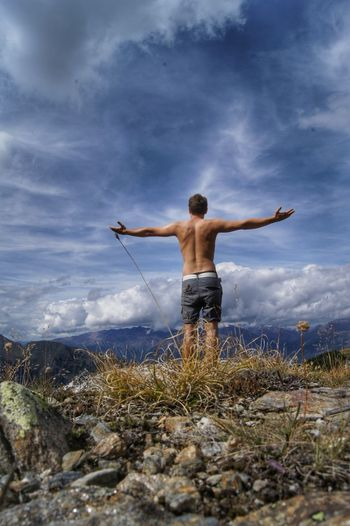 rear view of shirtless man standing on field against sky Alpen Südtirol Adult Adventure Arms Outstretched Beauty In Nature Cloud - Sky Day Full Length Grass Leisure Activity Men Mountain Nature One Man Only One Person Only Men Outdoors People Real People Rear View Scenics Shirtless Sky Standing Connected By Travel Lost In The Landscape