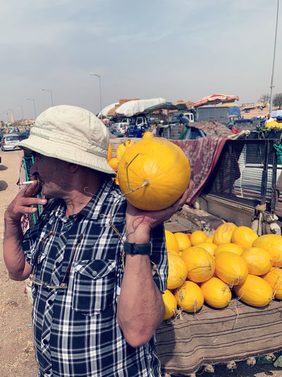 Man standing by fruits at market stall