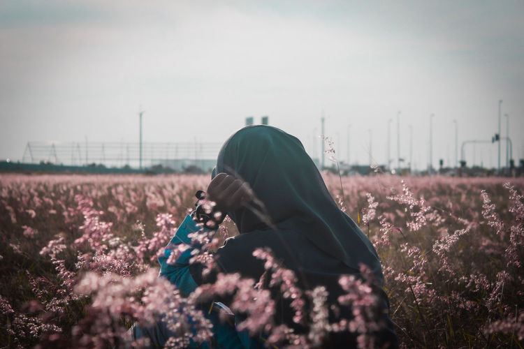 Close-up of woman standing in flowering field against sky