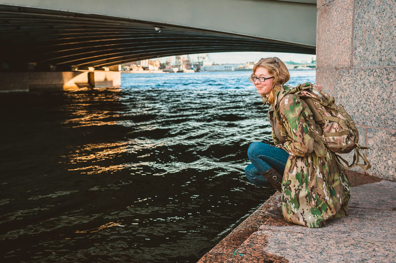 Young woman standing by water