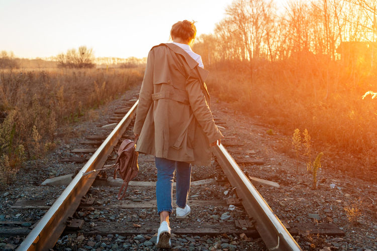 Fashion lifestyle portrait of young trendy woman dressed in brown coat, white shirt and jeans