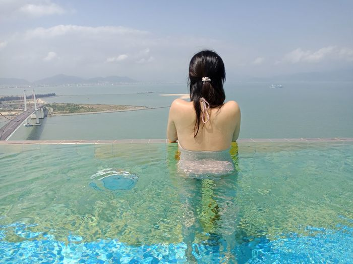 Rear view of young woman standing in infinity pool by sea