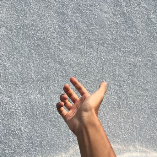 Cropped hand gesturing towards wall