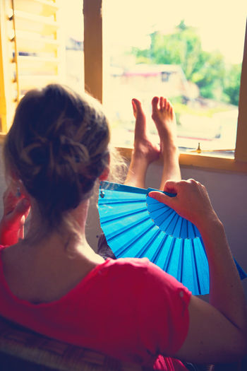 Rear View Of Woman Holding Blue Folding Fan While Sitting At Home