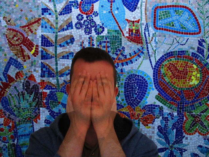 Digital composite image of young man sitting against mosaic wall
