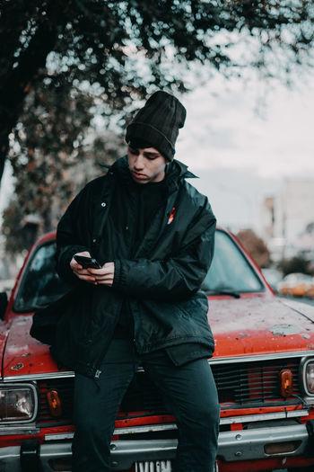Portrait of man standing against car