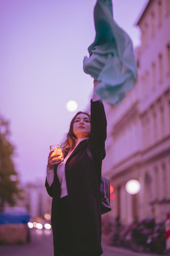 Beautiful woman moving green scarf while holding illuminated jar in city at dusk