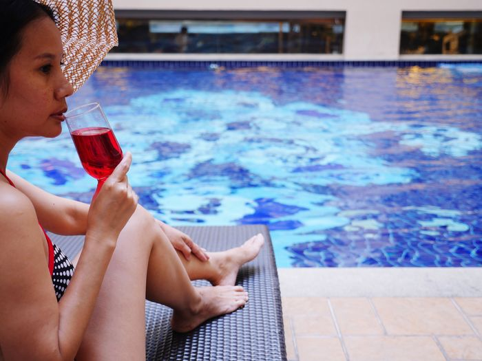 Mid Adult Woman Drinking On Lounge Chair At Poolside