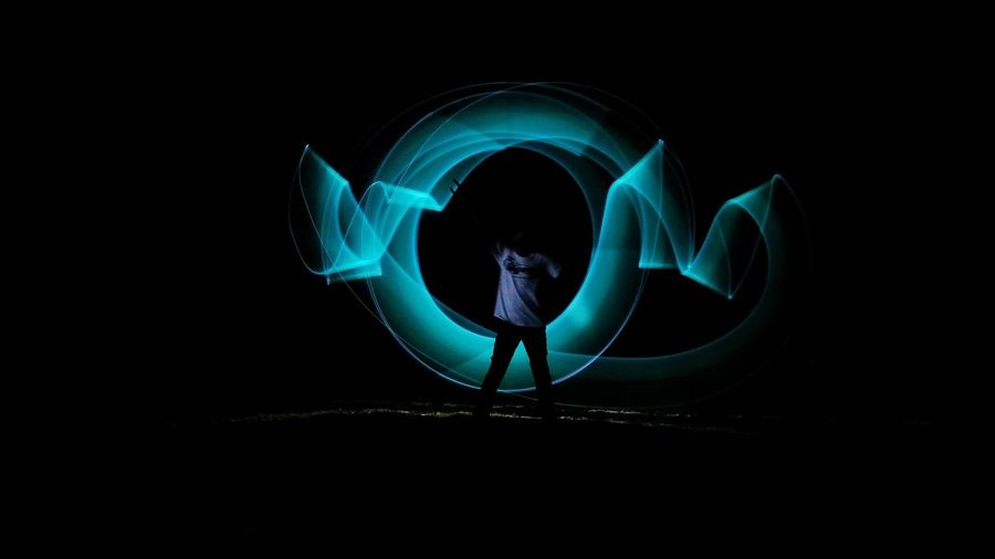 Man with light painting in dark