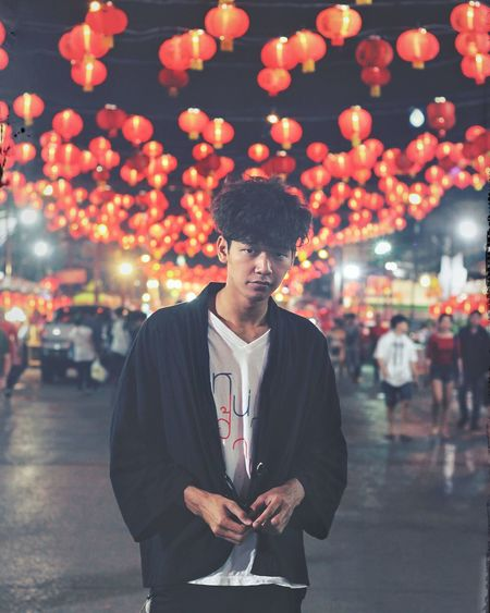 Portrait of young man standing against illuminated lanterns on road at night
