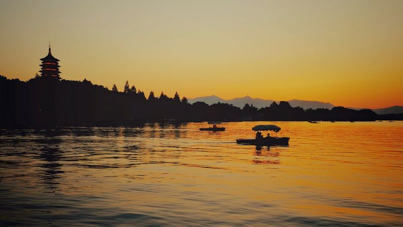 Sunset Lake Water Reflection Tranquility Outdoors Travel Destinations Mountain Scenics Landscape Beauty In Nature Lake View China View West Lake, Hangzhou Hangzhou,China Light And Shadow Yellow Vacations Warm Glow Travel Mountain Range Silhouette Summer Tranquility Boat
