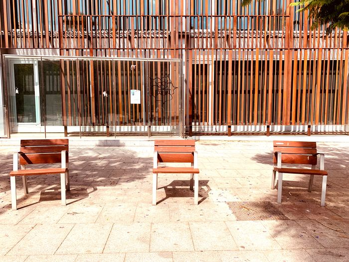 Empty bench against building