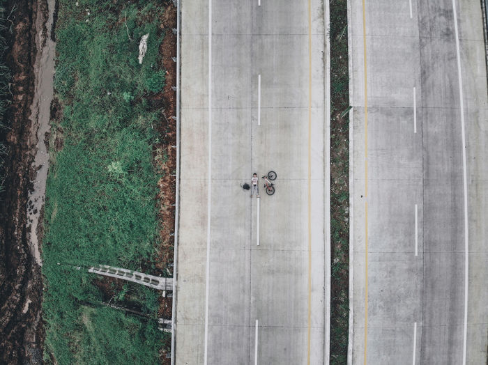 High angle view of a highway with boy laying on it