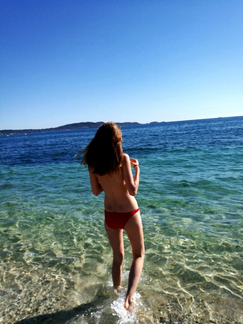 sea, real people, clear sky, one person, horizon over water, water, standing, leisure activity, nature, beach, lifestyles, bikini, beauty in nature, young adult, scenics, rear view, young women, full length, day, outdoors, sky, ankle deep in water