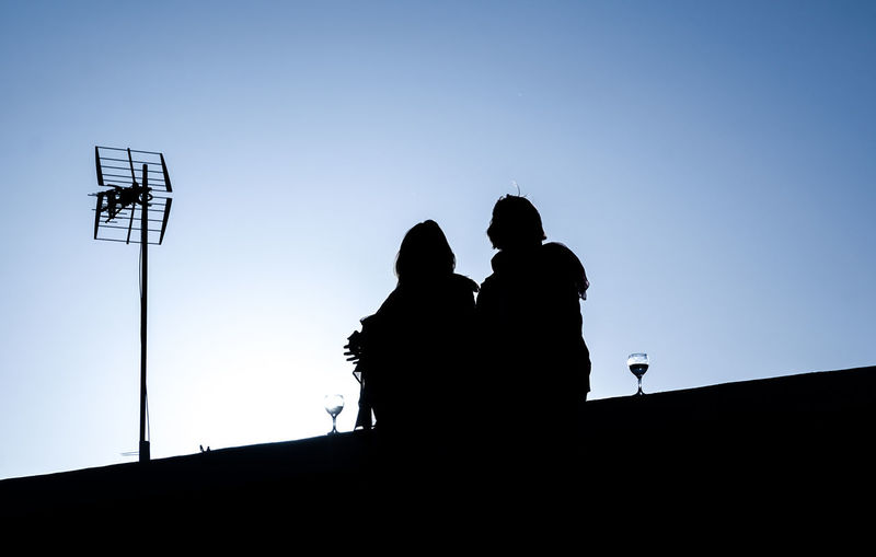 Low angle view of silhouette friends sitting with wineglasses on terrace against clear sky during sunset