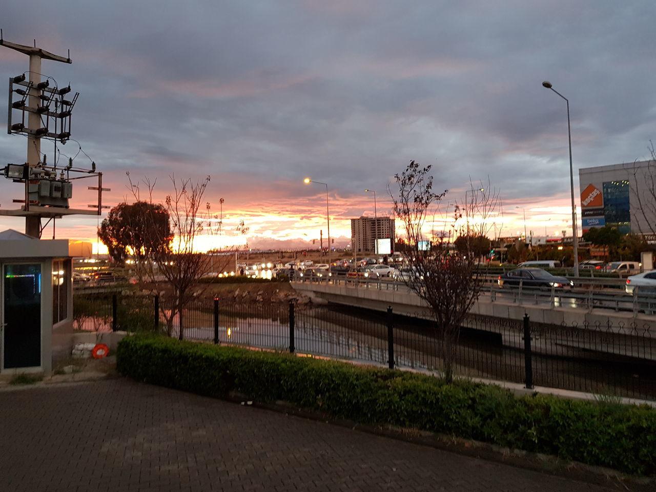 sky, cloud - sky, architecture, sunset, built structure, building exterior, city, transportation, nature, plant, illuminated, street, dusk, no people, tree, street light, road, mode of transportation, outdoors, car