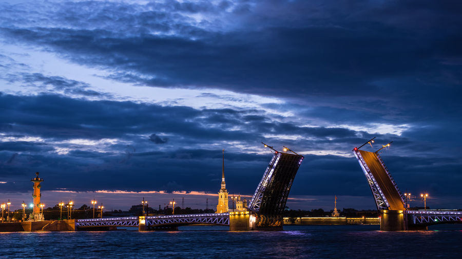 View of illuminated bridge on river against sky during dusk