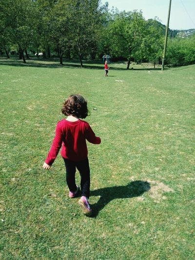 Rear view of girl walking on field in park