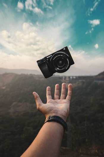 Midsection of person holding camera against sky