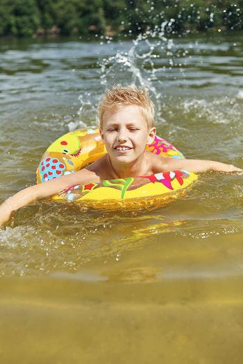 Smiling cute boy swimming in lake