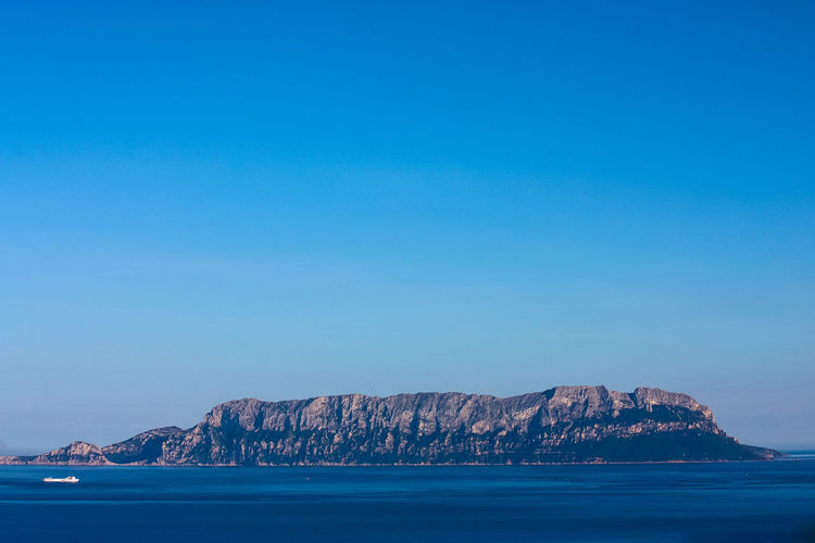 Scenic view of rock mountain by sea against clear blue sky
