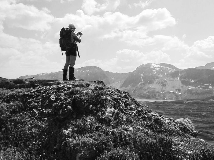 Hiker With Backpack Photographing On Mountain Against Sky