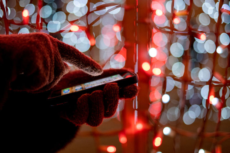 human hand using mobile at colorful bokeh background Illuminated Holding One Person Real People Focus On Foreground Lighting Equipment Using Phone Using Mobile Mobile Phone Christmas Lights Celebration Leisure Activity Christmas Lifestyles Close-up Glowing Light Night Decoration Colorful Sale Shopping Red Humanity Meets Technology