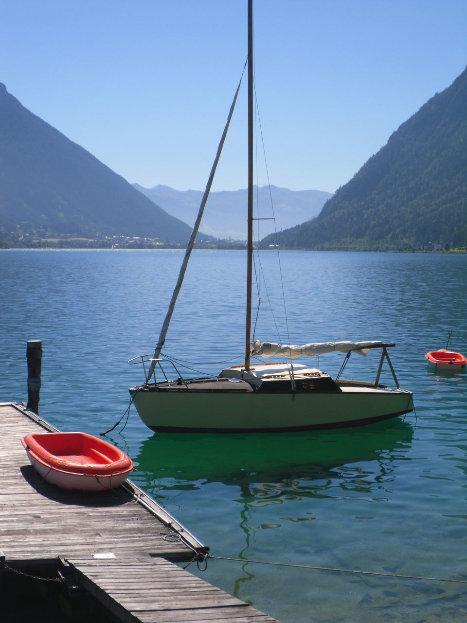 nautical vessel, water, mode of transportation, transportation, mountain, moored, beauty in nature, sky, nature, clear sky, scenics - nature, no people, day, lake, reflection, tranquility, outdoors, tranquil scene, sailboat, rowboat