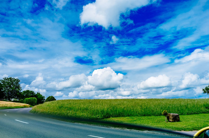 Road by green field against cloudy sky seen through car window