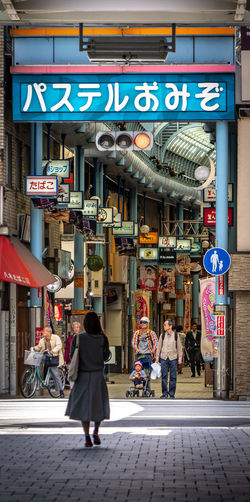 Architecture City Building Exterior Built Structure Street Walking Real People People City Life Communication Women Full Length Adult Incidental People Text Lifestyles Store Sign Men Rear View Outdoors