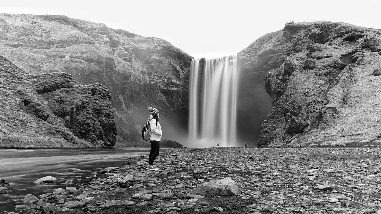 real people, full length, one person, nature, rock - object, casual clothing, beauty in nature, leisure activity, standing, motion, water, rear view, lifestyles, waterfall, clear sky, long exposure, outdoors, scenics, day, mountain, adventure, young adult, young women, men, tree, sky