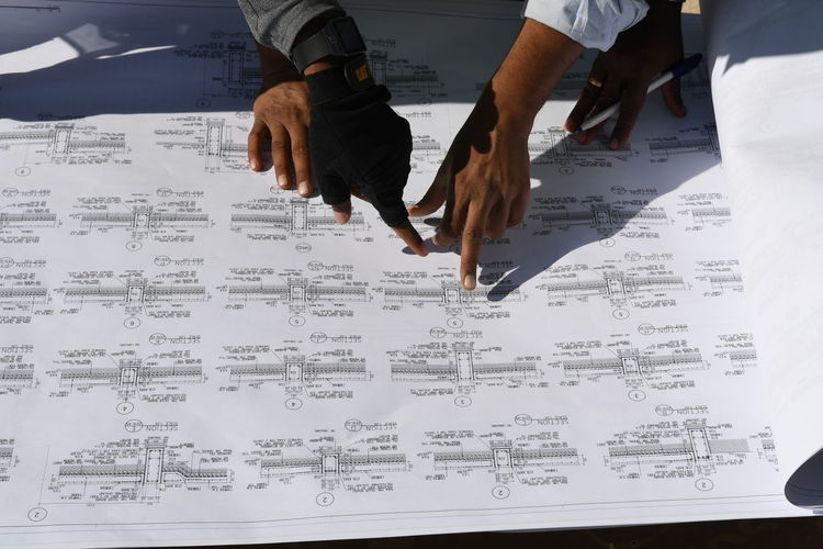Cropped hands of architects looking at blueprint