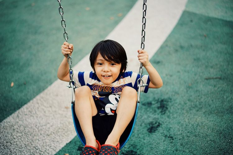 Portrait of a smiling girl sitting on swing at playground