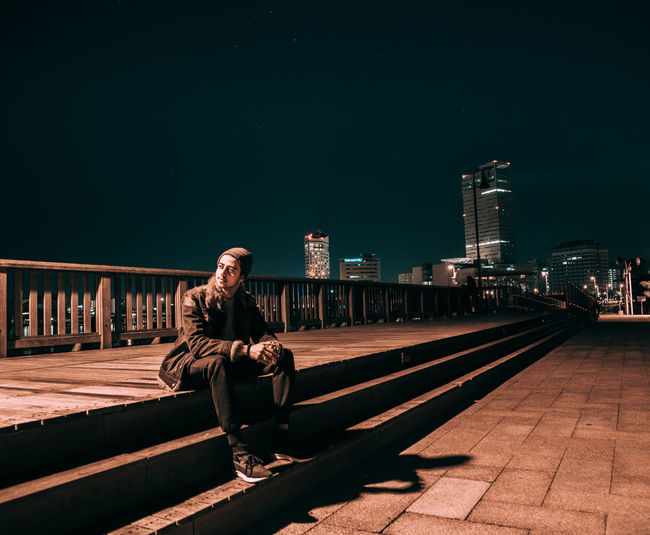 Young man sitting on footpath at night