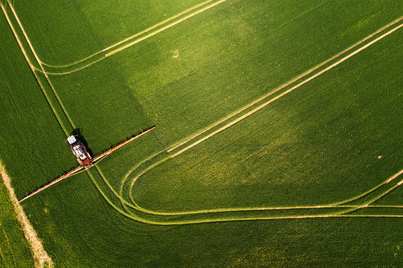 Top down view of the tractor spraying the chemicals on the large green field