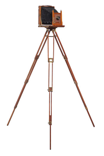 An antique wood camera with bellows atop an old wooden tripod isolated on white White Background Equipment Antique Camera Bellows Lens - Optical Instrument Wood - Material Tripod Old Vintage Large Format Isolated Cut Out Black Brown Photographic Object Color Image Photography No People Standing 1880s 1890s Shutter Aperture