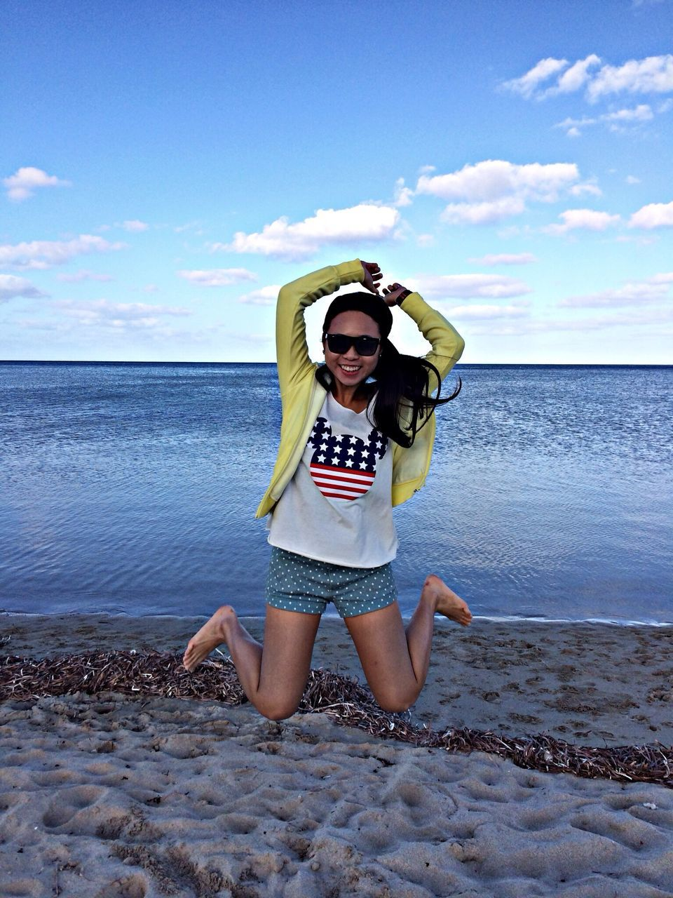 sea, one person, real people, sky, sunglasses, young adult, water, front view, beach, horizon over water, young women, cloud - sky, day, leisure activity, beauty in nature, nature, scenics, full length, standing, outdoors, happiness, lifestyles, vacations, smiling, beautiful woman, people