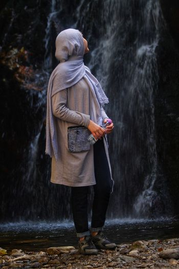 Woman standing by waterfall in forest