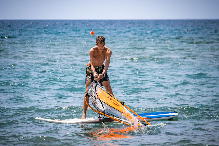 Full length of shirtless man standing on surfboard against sky